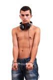 Hombre joven serio con las esposas y los auriculares que llevan Fotografía de archivo