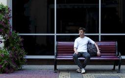 Hombre joven serio con una mochila que se sienta en un banco Imagen de archivo libre de regalías