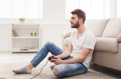Hombre joven serio en casa que juega a los videojuegos Imagen de archivo