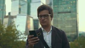 Hombre joven serio en un traje usando su smartphone y caminar, ciudad de Moscú