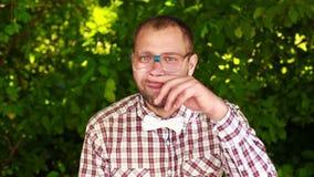 Hombre joven serio en vidrios que mira fijamente en la cámara y el frotamiento almacen de video