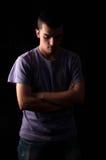 Hombre joven serio que se coloca con los brazos cruzados Fotografía de archivo libre de regalías