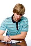 Hombre joven serio que se sienta en un escritorio. Fotografía de archivo