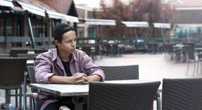 Hombre joven serio que se sienta en una tabla en un café Imagen de archivo