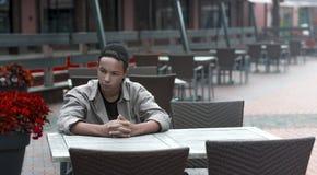 Hombre joven serio que se sienta en una tabla en un café Fotos de archivo libres de regalías