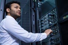 Hombre joven serio que trabaja con tecnología informativa Fotografía de archivo libre de regalías