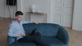Hombre joven serio y enfocado que se sienta en el sofá en sitio acogedor y contenido de observación con el ordenador portátil Ind almacen de metraje de vídeo