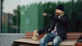 Hombre joven sin hogar borracho que habla con la gente que camina cerca del alcohol él y de la bebida que se sienta en banco en l foto de archivo libre de regalías