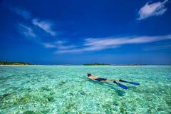 Hombre joven snorkling en laguna tropical con las casas de planta baja excesivas del agua, Maldivas imagenes de archivo