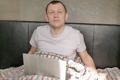 Hombre joven soñador que se sienta en cama con un ordenador portátil bajo cubiertas foto de archivo libre de regalías