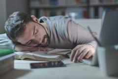 Hombre joven soñoliento en el escritorio imagen de archivo