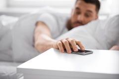Hombre joven soñoliento que alcanza para el smartphone en cama fotos de archivo