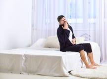 Hombre joven soñoliento que se sienta y que bosteza en cama en casa Despertar concepto Machista con conseguir inactivo de la barb imagen de archivo libre de regalías