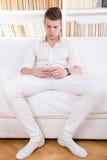 Hombre joven solo en el mensaje que manda un SMS blanco en el teléfono móvil Imágenes de archivo libres de regalías