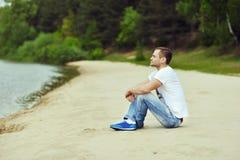 Hombre joven solo que se sienta cerca de un lago en un bosque Foto de archivo libre de regalías