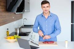 Hombre joven sonriente atractivo que cocina la carne en la cocina Imagen de archivo libre de regalías