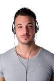 Hombre joven sonriente atractivo que escucha la música con los auriculares imagen de archivo libre de regalías
