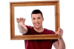 Hombre joven sonriente con el marco fotos de archivo libres de regalías