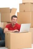 Hombre joven sonriente con el ordenador portátil en la caja Imagen de archivo