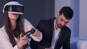 Hombre joven sonriente con el teléfono que intenta parar a la muchacha en auriculares de VR de jugar tanto Foto de archivo libre de regalías