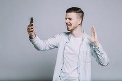 Hombre joven sonriente con la barba en una camisa blanca Foto de archivo