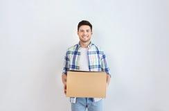 Hombre joven sonriente con la caja de cartón en casa Fotos de archivo libres de regalías