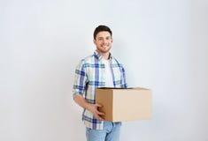Hombre joven sonriente con la caja de cartón en casa Foto de archivo