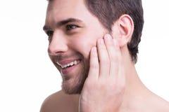 Hombre joven sonriente con la mano cerca de la cara. Fotos de archivo