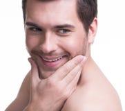 Hombre joven sonriente con la mano cerca de la cara Foto de archivo