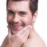 Hombre joven sonriente con la mano cerca de la cara Imagen de archivo libre de regalías