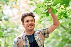 Hombre joven sonriente con la mochila que camina en bosque Imagen de archivo