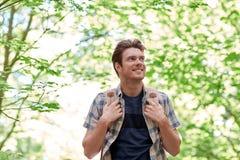 Hombre joven sonriente con la mochila que camina en bosque Fotografía de archivo