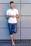 Hombre joven sonriente con los auriculares contra la pared Imágenes de archivo libres de regalías