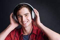 Hombre joven sonriente de Delighetd que escucha la música Fotografía de archivo libre de regalías