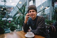 Hombre joven sonriente del inconformista en vidrios y una camisa, hablando en el teléfono el café está en la tabla Fotos de archivo libres de regalías