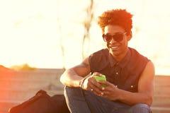 Hombre joven sonriente del inconformista urbano que usa el teléfono elegante Imágenes de archivo libres de regalías