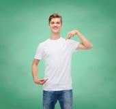 Hombre joven sonriente en camiseta blanca en blanco Foto de archivo