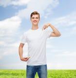 Hombre joven sonriente en camiseta blanca en blanco Fotos de archivo
