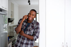 Hombre joven sonriente en casa usando el teléfono móvil Fotos de archivo libres de regalías