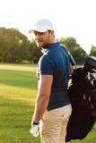 Hombre joven sonriente en el casquillo que sostiene la bolsa de golf Fotos de archivo