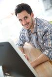 Hombre joven sonriente en el funcionamiento de la oficina Foto de archivo