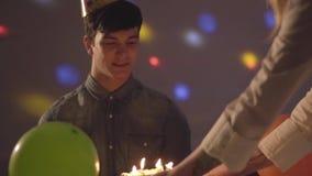 Hombre joven sonriente en el sombrero del cumpleaños que se sienta en la tabla Luces brillantes de diversos colores en la pared i metrajes