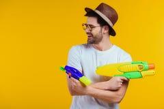 hombre joven sonriente en el sombrero y las gafas de sol que juegan con los armas de agua fotos de archivo