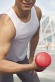 Hombre joven sonriente en el top sin mangas blanco que ejercita con pesa de gimnasia, primer, midsection, al aire libre en Pekín Fotografía de archivo