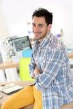 Hombre joven sonriente en la oficina Imagenes de archivo