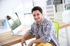 Hombre joven sonriente en la oficina Imagen de archivo libre de regalías
