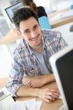 Hombre joven sonriente en la oficina Foto de archivo libre de regalías