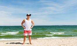 Hombre joven sonriente en la playa del verano Imagenes de archivo