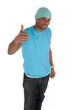 Hombre joven sonriente en un azul con el pulgar para arriba Imágenes de archivo libres de regalías