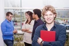 Hombre joven sonriente en un campus de la universidad Imagenes de archivo